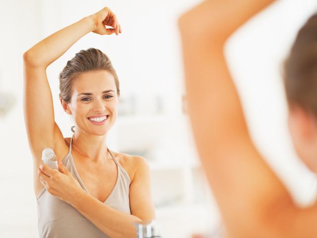 Smiling young woman applying roller deodorant on underarm in bathroom